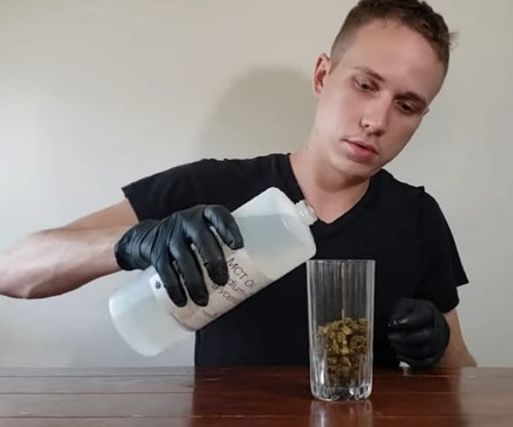 pouring coconut oil over decarbed buds